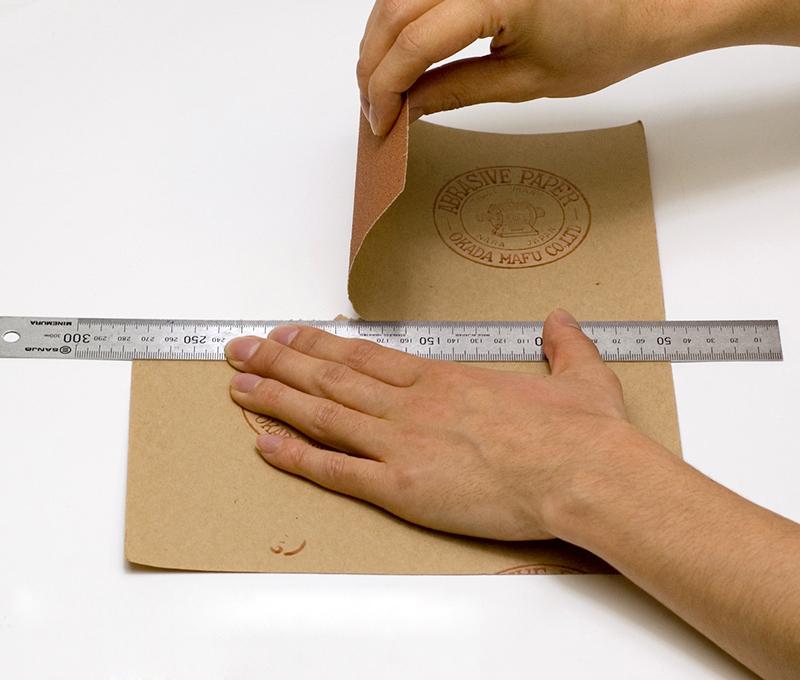 サンドペーパーを裏返して定規をあて、手で切り取ります