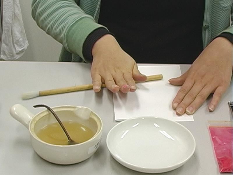 手順1.二つ折りにした紙に水干絵具を挟んで、筆の軸を転がしてつぶします。 (多量溶く場合は空ずりする)