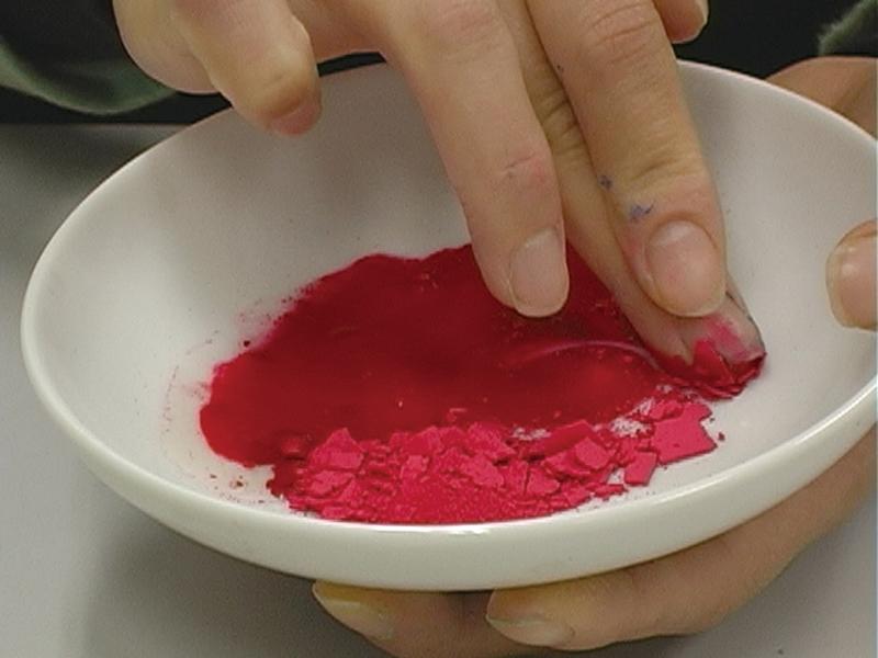 手順2.つぶした水干絵具を絵皿に取り、少しずつ膠液を加えて、中指の腹を使ってよく練ります。中指の上に人さし指を乗せると、力が入って溶き下ろしやすくなります。